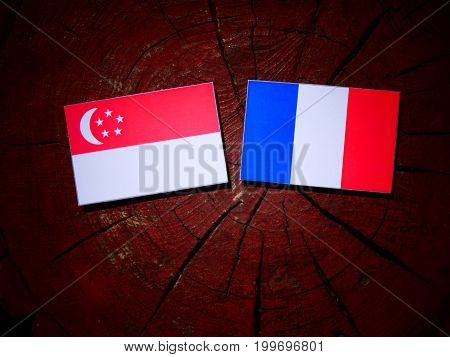 Singaporean Flag With French Flag On A Tree Stump Isolated