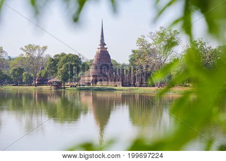 Branches of tree in the foreground Ancient buddha statue and pagoda at Sukhothai Historical Park Sukhothai Province Thailand.