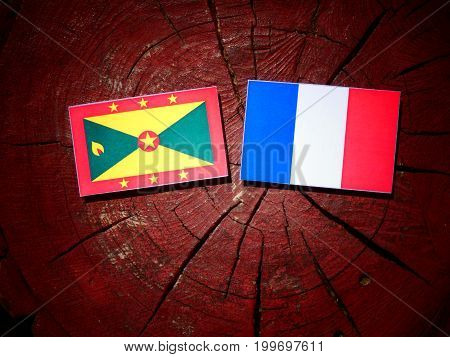 Grenada Flag With French Flag On A Tree Stump Isolated