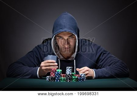 Young man wearing a hoodie with cards and chips gambling