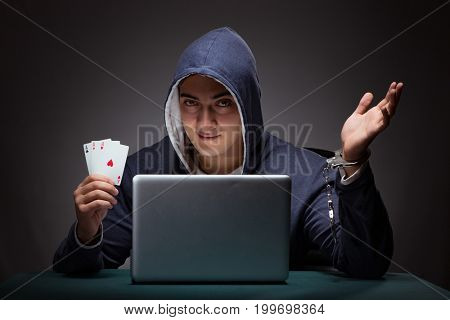 Young man in handcuffs wearing a hoodie sitting in front of a la