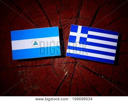 Nicaraguan Flag With Greek Flag On A Tree Stump Isolated