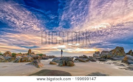 Mui Ne, Vietnam - December 5th, 2016: Young woman alone standing alone on volcanic rock look on horizon immensity of dawn like aspirations, hoping good things for the future in Mui Ne, Vietnam