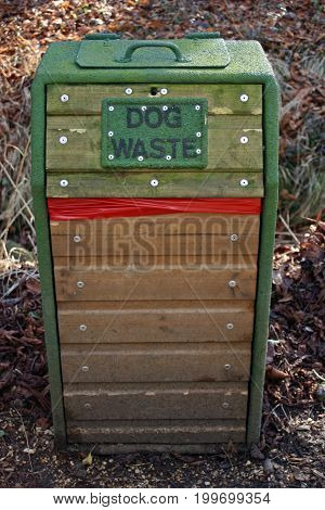 Green wooden dog waste bin with a metal frame in woodland. Red plastic bag for the waste showing. Background of dead leaves.