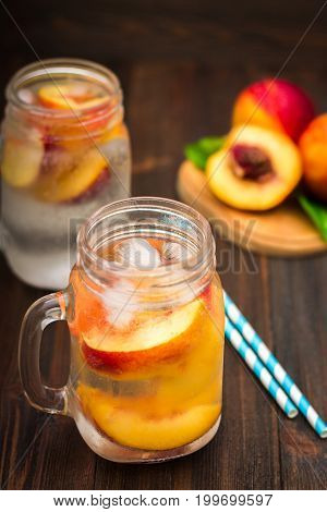 Mason Jar Glass Of Homemade Peach Iced Water On A Rustic Wooden Background.