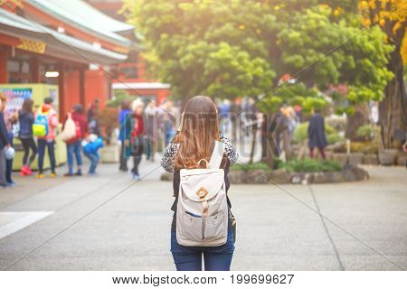Woman from behind has backpack in Autumn season at Senso-ji temple in Asakusa District a major tourist attraction in Tokyo Japan