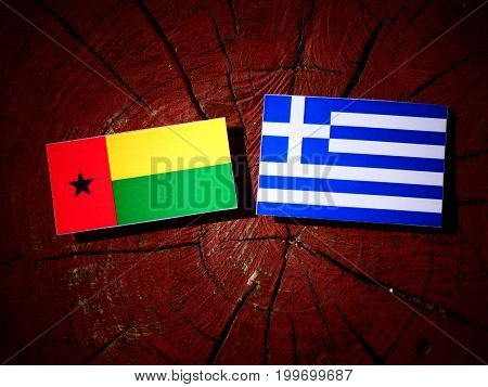 Guinea Bissau Flag With Greek Flag On A Tree Stump Isolated
