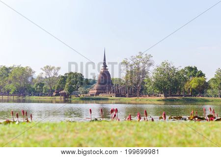 Ancient buddha statue and pagoda with lotus in the pool at Sukhothai Historical Park Sukhothai Province Thailand.