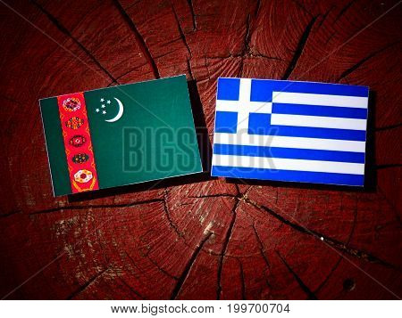 Turkmenistan Flag With Greek Flag On A Tree Stump Isolated