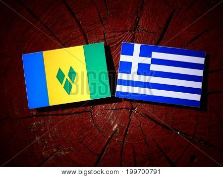 Saint Vincent And The Grenadines Flag With Greek Flag On A Tree Stump Isolated