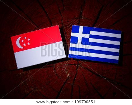 Singaporean Flag With Greek Flag On A Tree Stump Isolated