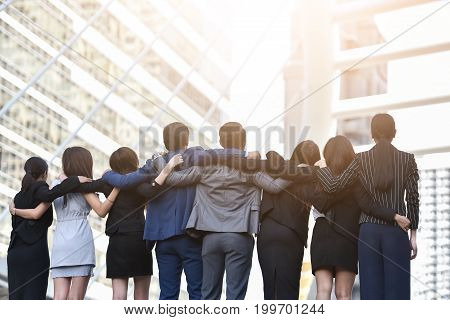 Rear view of Happiness Group Business People Celebrating with hugging at outdoor. Successful Concept.