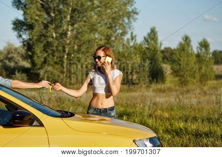 Couple in love. Road adventure. The guy gives the girlfriend the keys of the ignition. The girl is talking on the cell phone while standing by the car.