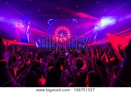 Picture of concert, music festival,party in nightclub, dance floor, disco club, many people standing with raised hands up and clapping, happiness and night life concept.