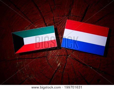 Kuwaiti Flag With Dutch Flag On A Tree Stump Isolated