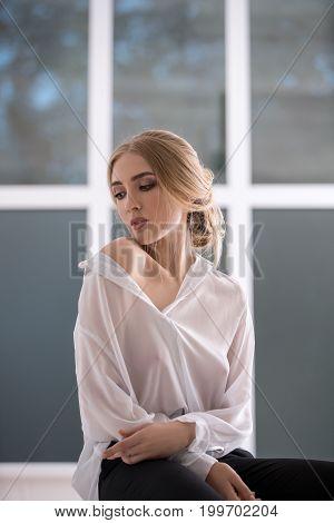 Woman wearing sexy white shirt sitting on window sill studio portrait