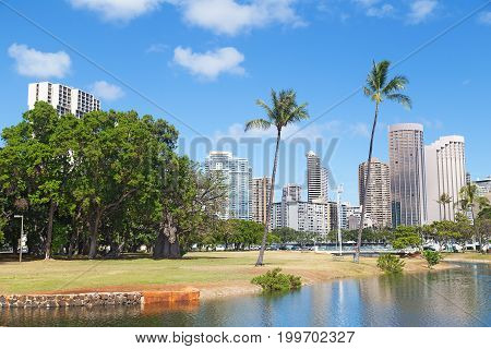 Honolulu in an early morning Hawaii USA. Palms and buildings under Hawaiian sun and clouds in the sky.