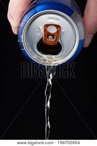 Pouring beer from metal can isolated on black background