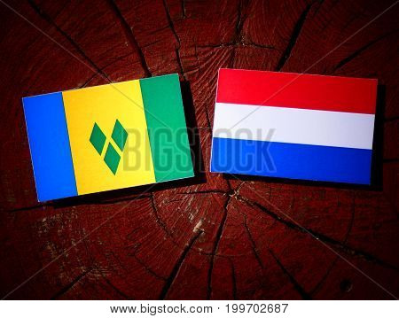 Saint Vincent And The Grenadines Flag With Dutch Flag On A Tree Stump Isolated