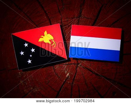 Papua New Guinea Flag With Dutch Flag On A Tree Stump Isolated