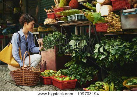 Japanese smiling woman choosing greenery for the salad ta market
