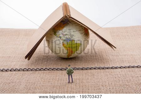 Figurine And Globe On Canvas With A Chain