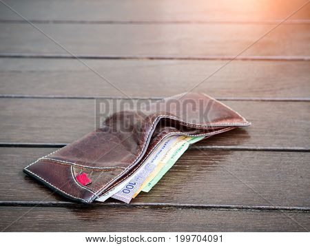 Lost leather wallet with money on empty bench lost money concept copy space on top.