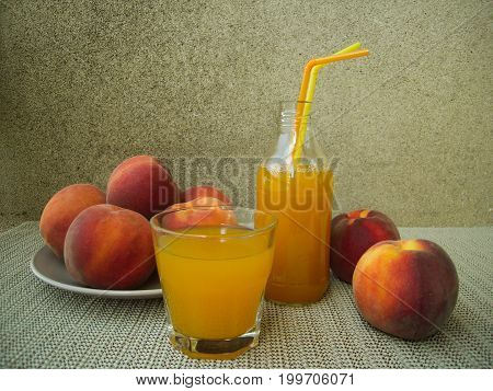 Peach juice and whole peaches in the rustic set.