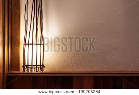 Opened lamp made of branch on wooden head bed and white wall, with copy space