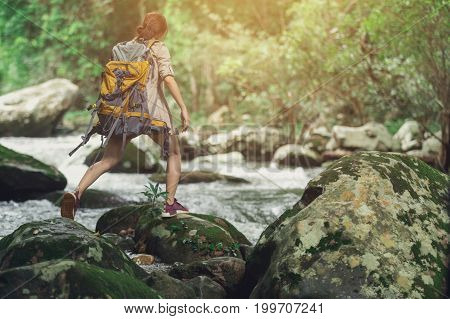 Trekkers jump over rocks with streams flowing through the concept of a breakthrough with barriers to work.