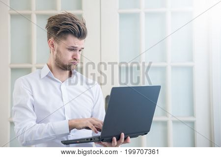 Young businessman looking laptop notebook with shocked negative stress posture in office