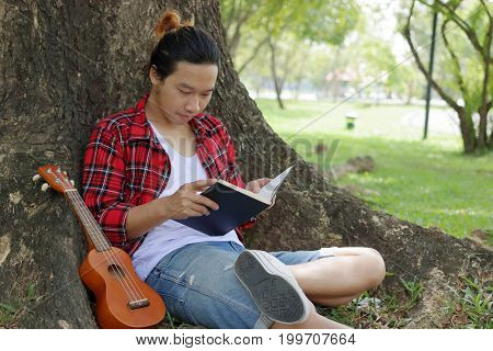Young man reading book in the park with ukulele