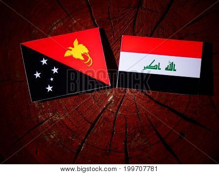 Papua New Guinea Flag With Iraqi Flag On A Tree Stump Isolated
