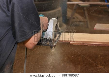 Electric circular saw is being sawed a piece of wood by senior worker in carpentry workshop.