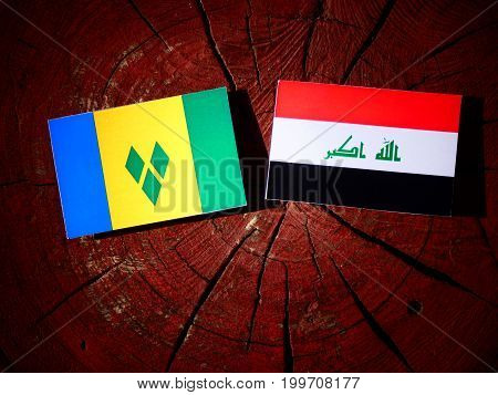 Saint Vincent And The Grenadines Flag With Iraqi Flag On A Tree Stump Isolated