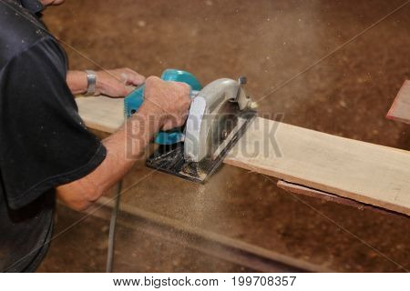 Electric circular saw is being cut a piece of wood against hands of senior carpenter in carpentry workshop.