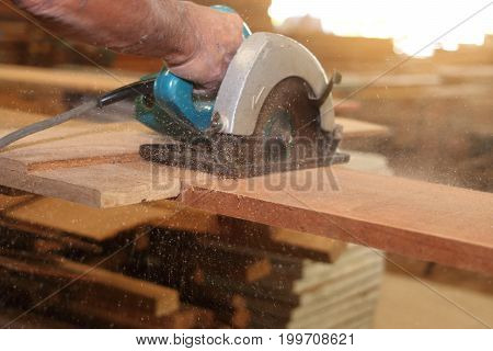 Selective focus on piece of wood is being cut with electric circular saw against hands of worker in carpentry workshop with sunshine effect background.