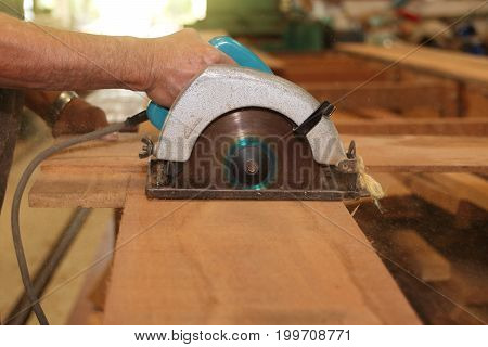 Front view of hands of senior carpenter cutting a piece of wood against electric circular saw in carpentry woodshop. Woodworking concept