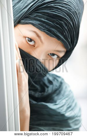Oriental lady in black hijab hiding. Vertical photo