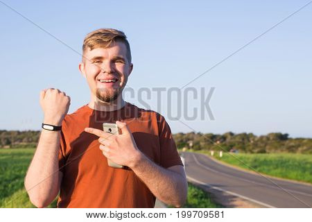 fitness, sport, training and lifestyle concept - close up of young man with heart-rate watch bracelet in summer park