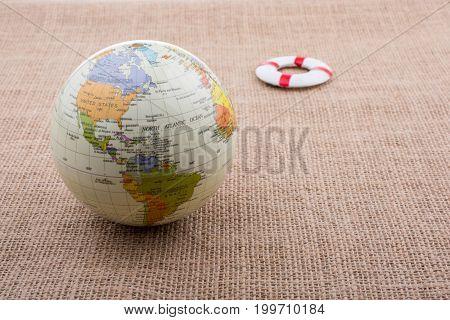 Life Preserver Beside A Globe On Canvas