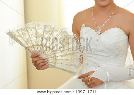 Wedding ceremony accessories. Bride holding a fan in her hands. Luxury white dress details