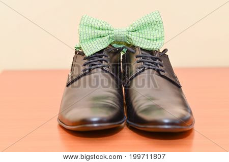 Wedding accessories. Groom black leather shoes and green bow tie  details