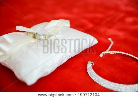Wedding bride accessories. Wedding rings on white pillow and necklace