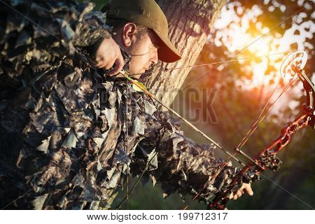 hunter with bow hunting in the forest