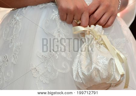 Wedding accessories.Bride holding a white wedding purse in her hands; close up details of handscand purse