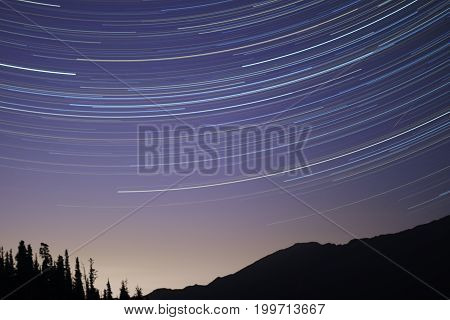 round startrail in the night with hill and trees in foreground