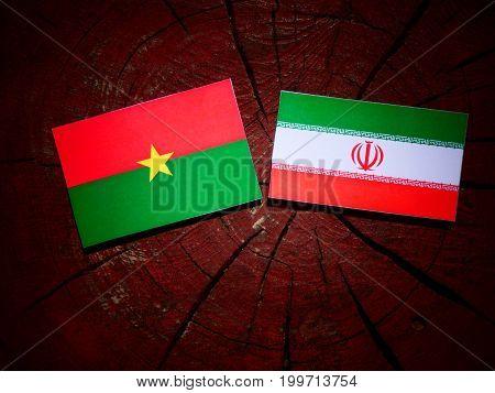 Burkina Faso Flag With Iranian Flag On A Tree Stump Isolated