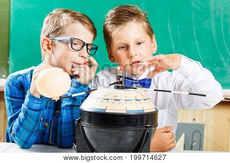 Two schoolboys learning model of solar system in school