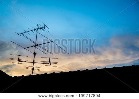 television antenna on roof with blue sky in the evening